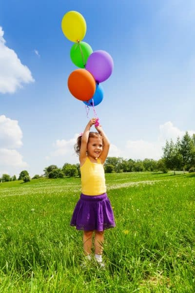 Little girl with flying balloons in the air in the park