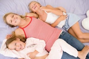 mom and kids on bed smiling