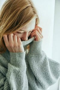 girl smelling sweater