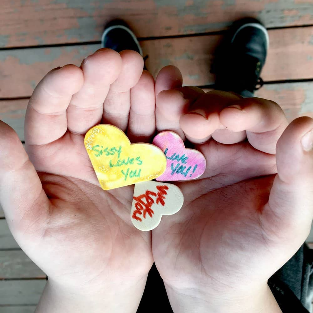 child holding heart shaped wood chips